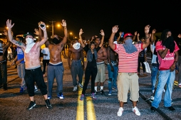 Demonstrators gesture with their hands up after protests in reaction to the shooting of Michael Brown turned violent near Ferguson, Missouri August 17, 2014.