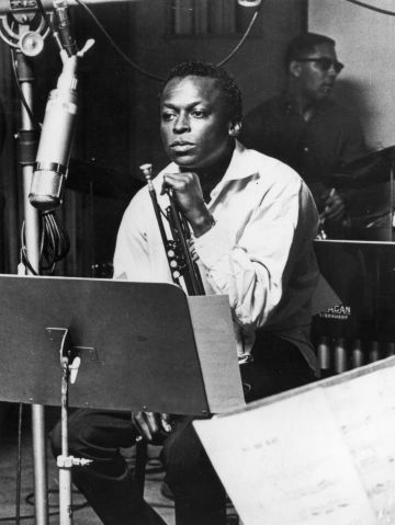 American jazz trumpeter and composer Miles Davis (1926 - 1991), sits with his instrument during a studio recording session, October 1959. (Photo by Hulton Archive/Getty Images)